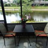 Terrasse avec vue sur le lac, table de patio avec 4 chaises et un BBQ